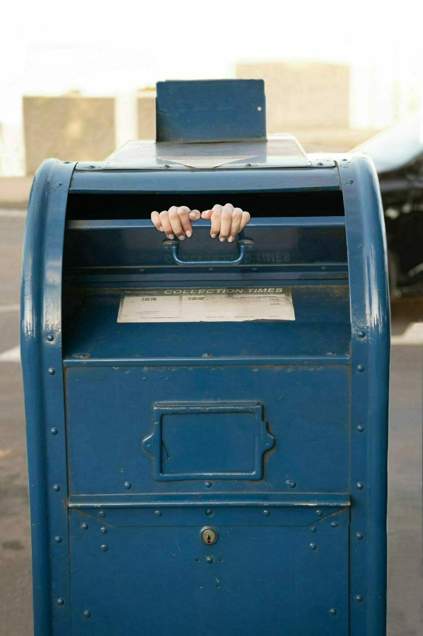 person inside blue steel mailbox