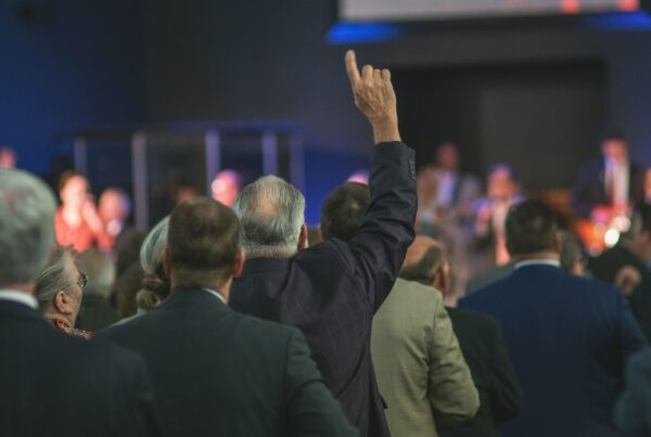man in black suit jacket standing in front of people
